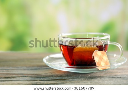 Black tea with bag in glass cup on green blurred background, close up - stock photo