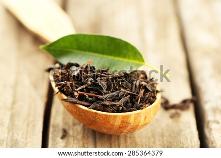 Black tea with leaf in spoon on old wooden table - stock photo