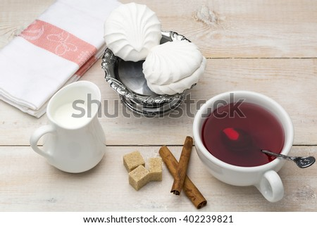 Black tea with milk. Cane sugar and cinnamon sticks with sweet dessert on wooden table - stock photo