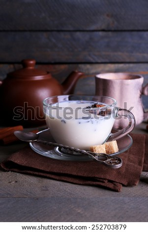 Black tea with milk in cups and teapot with lump sugar on color wooden planks background