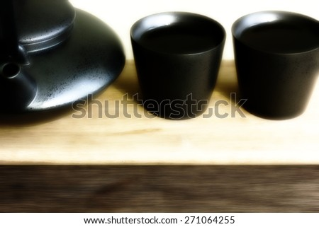 Black teapot and two teacups with tea on bamboo plate. Shallow DOF, Blur, Toning - stock photo