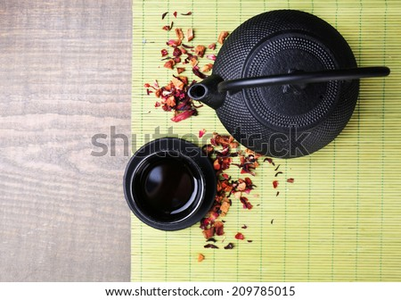 Black teapot, bowl and tea on wooden background  - stock photo