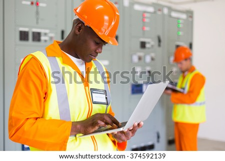 black technical worker using laptop with colleague on background - stock photo