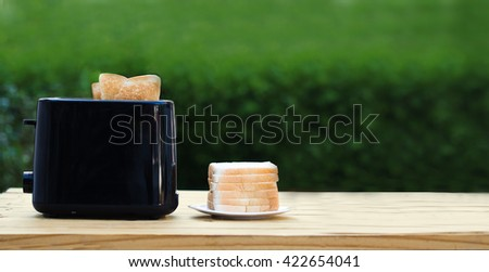 Black toaster with toasted bread slices on the wood - stock photo