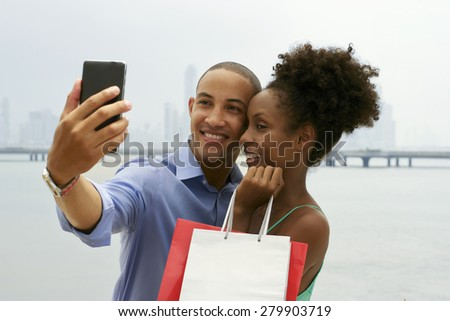 Black tourist heterosexual couple in Casco Antiguo Panama City with shopping bags. The man takes a selfie with his girlfiend and shopping bags with skyline in background - stock photo