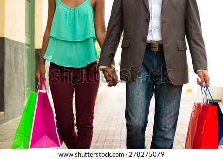 Black tourist heterosexual couple walking in the streets of Casco Antiguo in Panama City with shopping bags. Cropped view of man and woman holding hands - stock photo