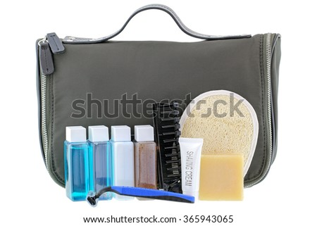 Black traveling cosmetic bag with toiletries in the front, isolated on white - stock photo