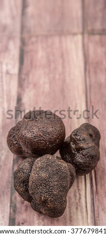 Black truffle mushroom over wooden background