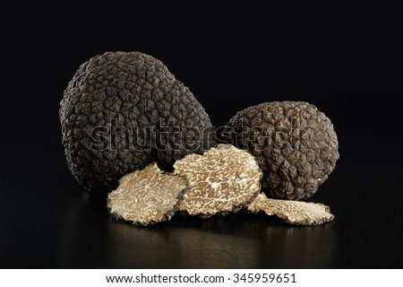 Black truffles and slices on black, clipping path included - stock photo