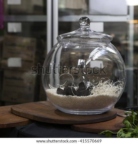 Black truffles in jar isolated for sale at the market - stock photo