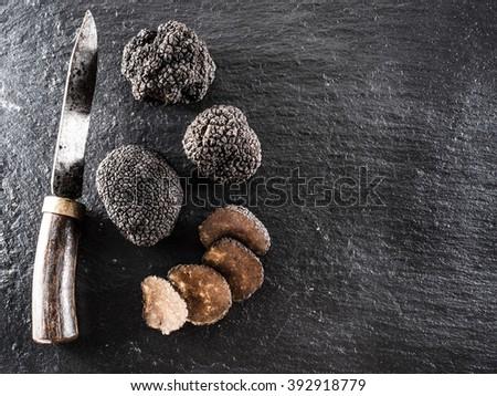Black truffles on the graphite board. - stock photo