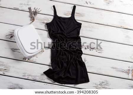 Black u-neck dress and purse. Dark dress on white shelf. Dark dress and white purse. Contrast of clothing and accessory. - stock photo