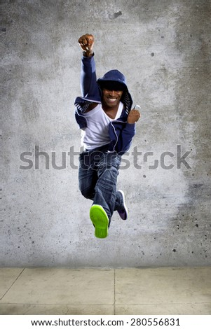 Black urban hip hop dancer jumping high on a concrete background - stock photo