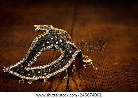 Black Venice mask with golden decoration on rustic wooden table - stock photo