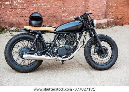 Black vintage custom motorcycle motorbike cafe racer with black full face helmet in front of brick wall. Ready for a lifestyle ride. - stock photo