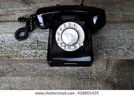 Black vintage phone on wooden background close-up, top view - stock photo