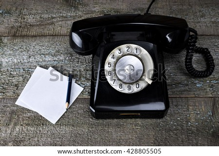 Black vintage phone on wooden background with pencil close-up, top view, pick up the phone - stock photo