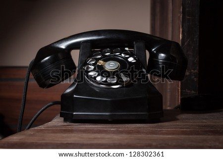 Black vintage telephone on a wooden surface - stock photo