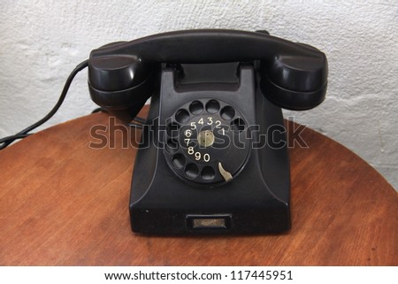 Black vintage telephone on wooden desk - stock photo