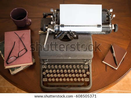 black vintage typewriter sitting on brown wooden table next to brown leather notepad and pen, and old books and stylish glasses. any author, writer, editor or journalist can type a creative story