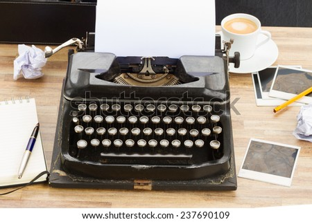 black vintage typewriter with empty white page on working table - stock photo