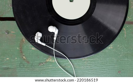 Black vinyl record disc with headphones on old green wooden desk - stock photo