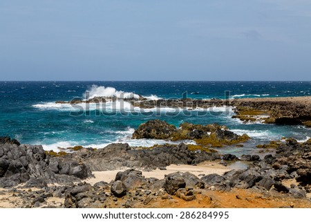 Black volcanic rock on shore of Aruba - stock photo
