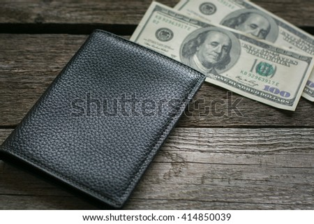Black wallet and american dollar on wooden board. - stock photo