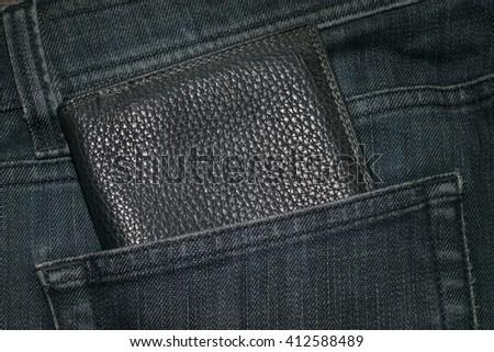Black wallet and blue jeans back pocket. - stock photo