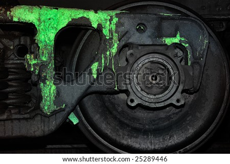 Black wheel of a train polluted by a paint of toxic colour - stock photo