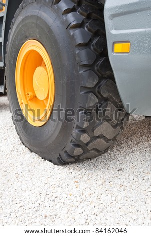 Black wheel with yellow disk of front loader on white stone road - stock photo