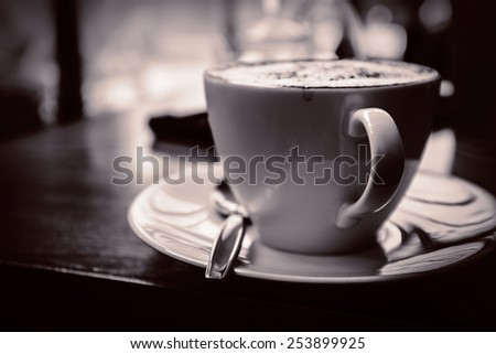 Black white A cup of Cappuccino with retro style coffee shop background memory under light classical - stock photo