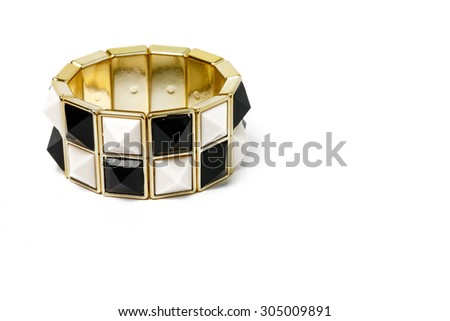 black, white and gold bracelet on white background. - stock photo