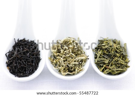 Black, white and green dry tea leaves in spoons - stock photo