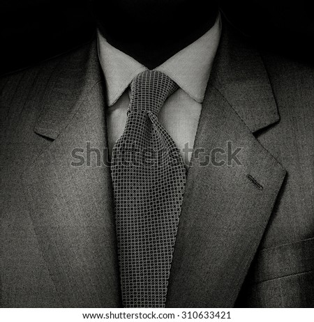 Black & White film photo. Man suit detail in a dark and sinister ambiance. - stock photo