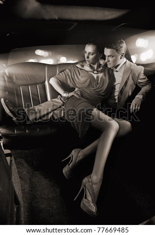 Black white image of a handsome couple hugging in a luxury limousine - stock photo
