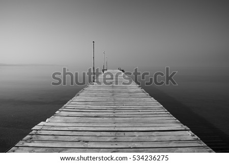 Black white photography of a wooden pier. Sea is so quiet.