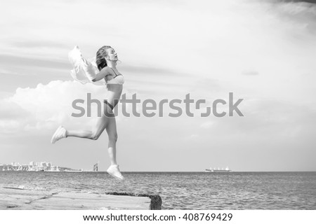 Black white photography of beautiful young lady enjoying dancing jumping over outdoors water sky background - stock photo