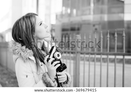 Black white photography of beautiful young lady holding photo camera on city glass building background - stock photo