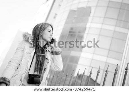Black white photography of beautiful young lady speaking on mobile phone on city glass building background - stock photo
