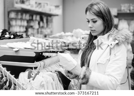 Black white photography of young beautiful female selecting or choosing for buying clothes on interior shop background - stock photo