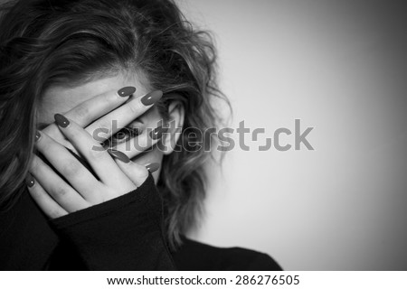 Black & White portrait of a young women hiding her face with her hands - stock photo