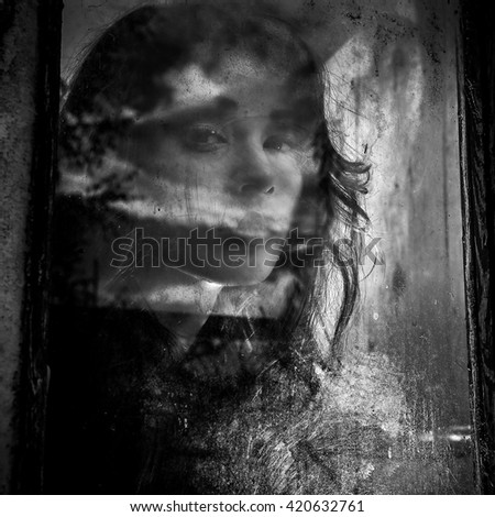 Black-white portrait of beautiful young spooky woman looks through grunge styled window.  - stock photo