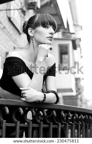 Black white portrait of pretty slim young woman model in black off-the-shoulder top, elegant earrings, nice hairstyle, leaning over balustrade of balcony, looking somewhere, dreaming, enjoying the day
