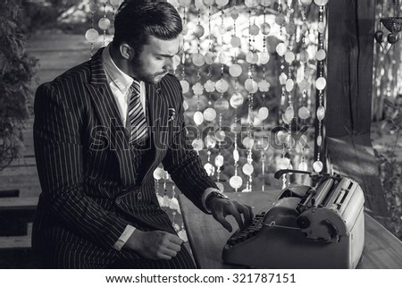 Black-white portrait of young beautiful fashionable man in classic suit in summer lodge near old typewriter.