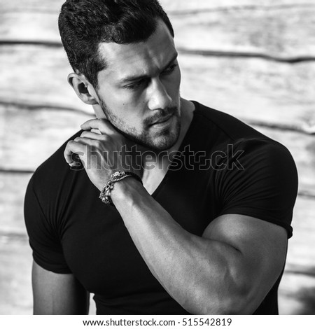 Black-white portrait of young beautiful sporty man in black t-shirt against wooden wall.