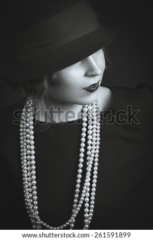 Black-white portrait of young beauty dark hair girl in vintage chanel 1920 style in red hat  - stock photo