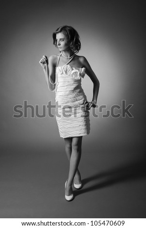 black & white portrait of young woman in white dress with pearl beads in retro style - stock photo