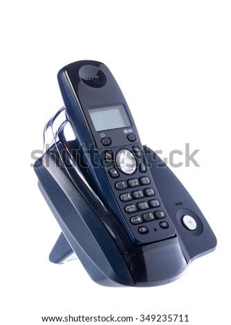 Black wireless phone resting on base. Retro phone - stock photo