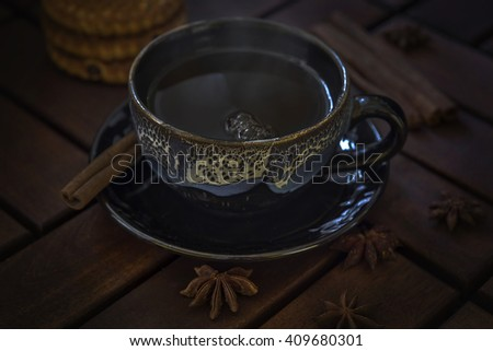 Black with blue ceramic cup on a table of dark wood. Three cookies with raisins. Cinnamon and star anise. - stock photo